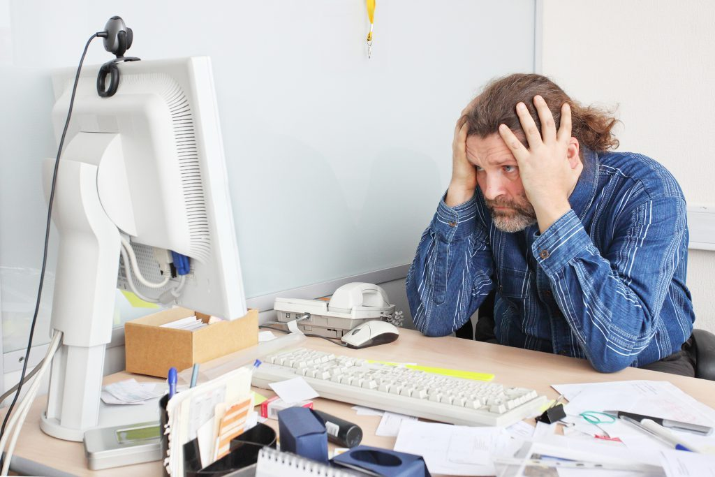 man looking at computer very stressed